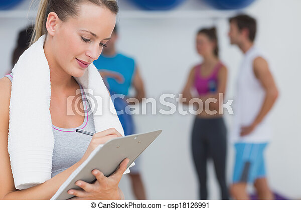 Female trainer writing on clipboard with fitness class in background at the gym - csp18126991