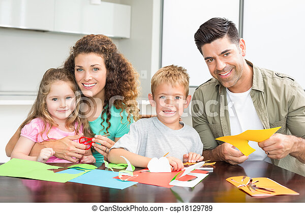 Smiling family doing arts and crafts together at the table - csp18129789