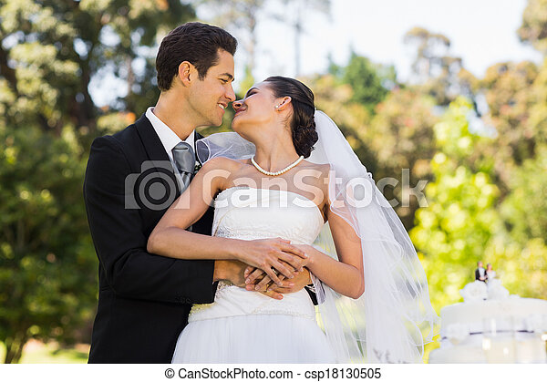 Newlywed about to kiss besides wedding cake at park - csp18130505