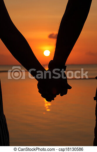 Silhouettes couples hands on sunset - csp18130586