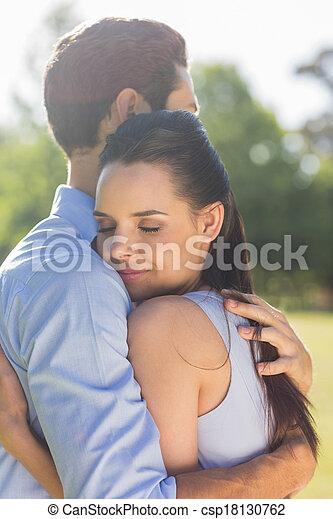 Young couple embracing at park - csp18130762