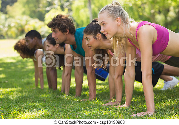 Group of fitness people doing push ups in park - csp18130963