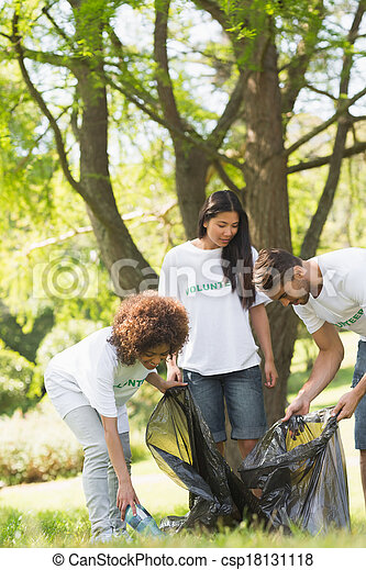 Team of volunteers picking up litter in park - csp18131118