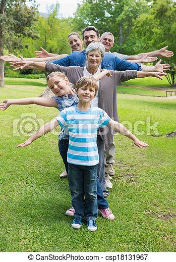 Extended family standing in row with arms outstretched at park - csp18131967