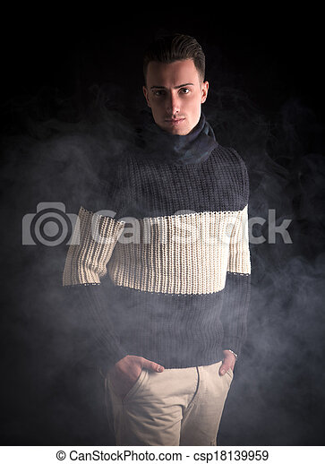 Good looking young man standing, wearing winter sweater  - csp18139959