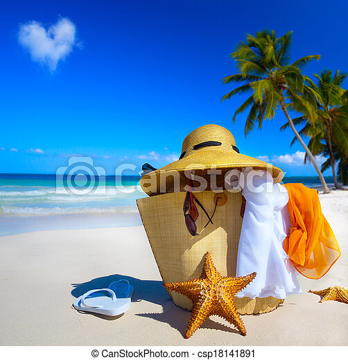 Art Straw hat, bag, sun glasses and flip flops on a tropical beach - csp18141891