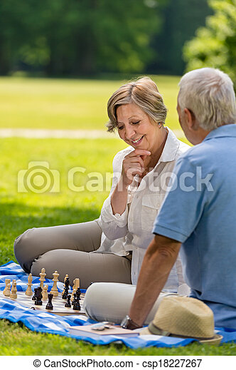 Elderly friends couple playing chess outdoors - csp18227267