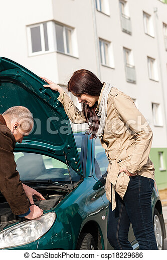 Man working on repairing a woman\'s car