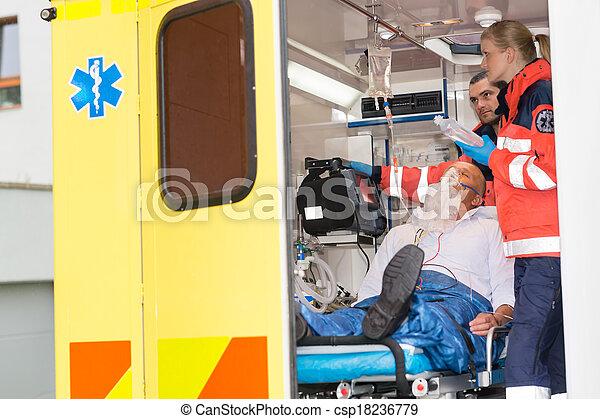 Paramedics checking IV drip patient in ambulance