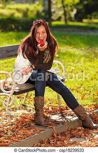Autumn attractive woman eat apple sunset park - csp18239533