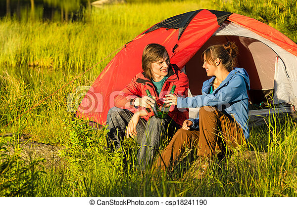 Camping teenagers drink beer outdoors