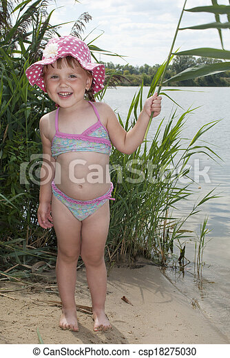 Summer on the lake near the reeds  little girl in panama hat. - csp18275030