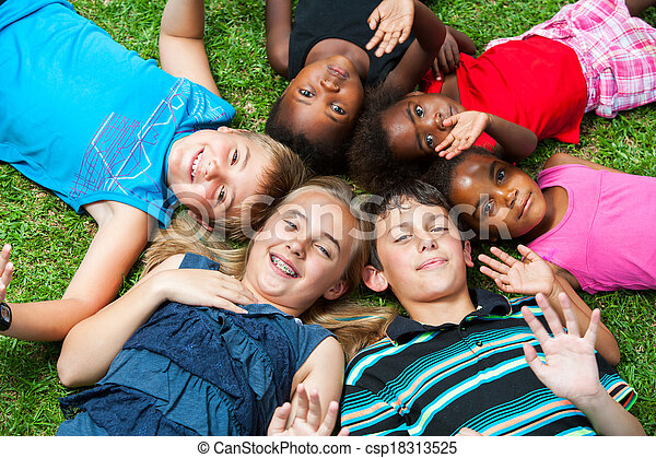 Diverse group og children laying together on grass. - csp18313525