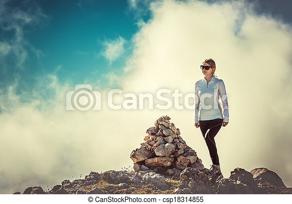 Woman Traveler on Mountain Summit with stones way sign and Clouds Sky on background Hiking Mountaineering Lifestyle summer - csp18314855