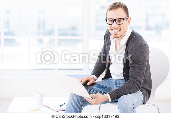 Creative executive. Handsome young man in glasses working on computer and smiling at camera while sitting at his working place - csp18317493