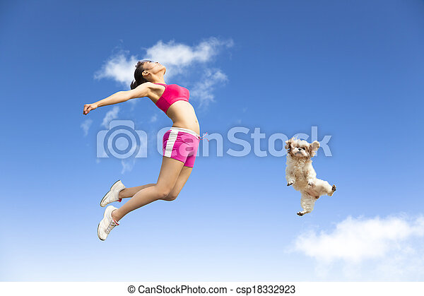 young woman and dog jumping in the sky - csp18332923