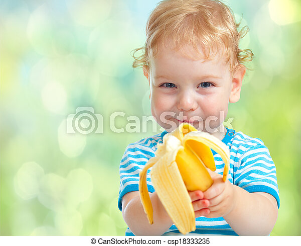 happy kid eating banana fruit. healthy food eating concept.  - csp18333235