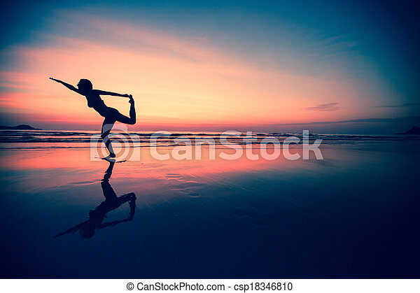 Silhouette of a woman practicing yoga on the beach at sunset. - csp18346810