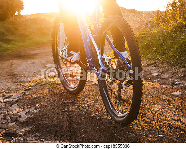 low angle view of cyclist riding mountain bike trail at sunrise - csp18355336