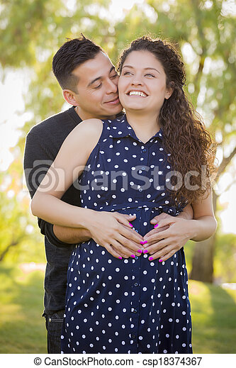 Hispanic Man Hugs His Pregnant Wife Outdoors At the Park - csp18374367