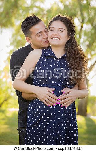 Hispanic Man Hugs His Pregnant Wife Outdoors At the Park - csp18374367