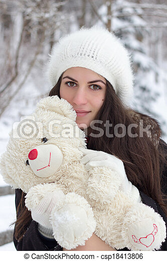 Cheerful Caucasian Young Woman in Snowy Weather holds a toy