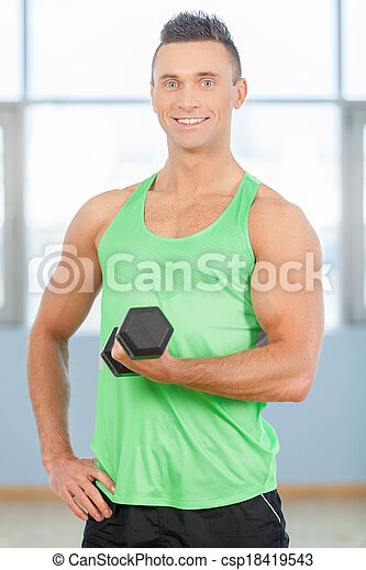 Fitness guy. Young handsome man in green shirt is lifting weights - csp18419543
