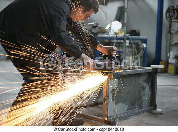 manual worker grinding steel table in production hall