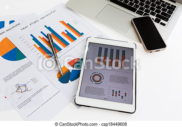 Financial charts on the table with tablet phone and pen - csp18449608