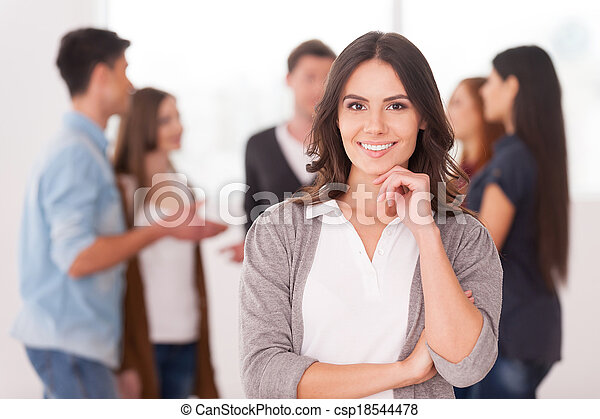 She is a team leader. Confident young woman holding hand on chin and smiling while group of people communicating on background - csp18544478