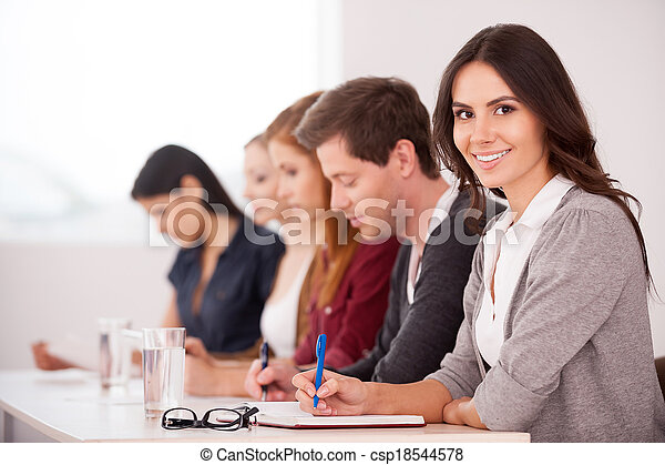 People at the seminar. Attractive young woman smiling at camera while sitting together with another people at the table - csp18544578