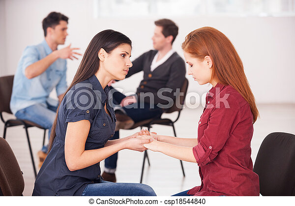 Helping each other to solve problems. Two depressed women sitting face to face and holding hands while two men communicating on background - csp18544840