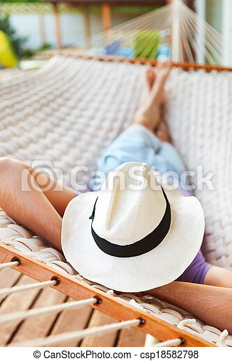 Man in hat in a hammock on a summer day - csp18582798