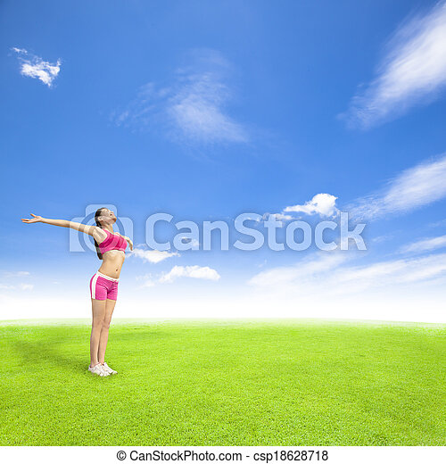 relaxing young woman standing on a meadow with blue sky - csp18628718