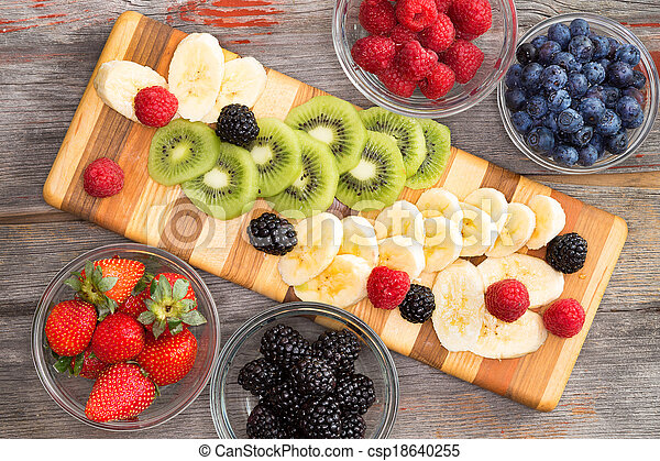 fruit salad with mixed berries in individual containers, sliced banana ...