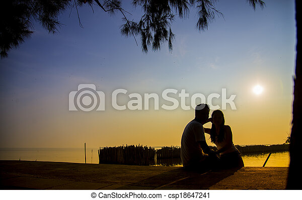 Lovely Couple sit in the sunset with silhouette scene4 - csp18647241
