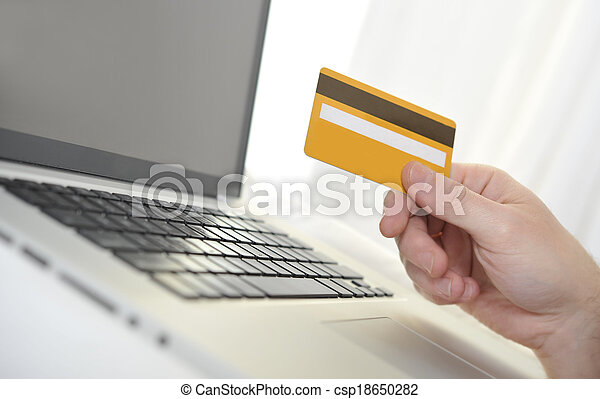 Man holding credit card in hand online shopping and banking - csp18650282