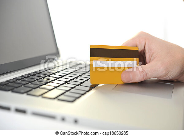 Man holding credit card in hand online shopping and banking - csp18650285