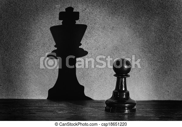 Chess pawn standing in a spotlight that make a shadow of king with darkness actistic conversion - csp18651220