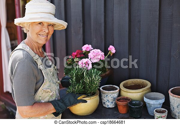 Senior woman planting flowers in a pot - csp18664681