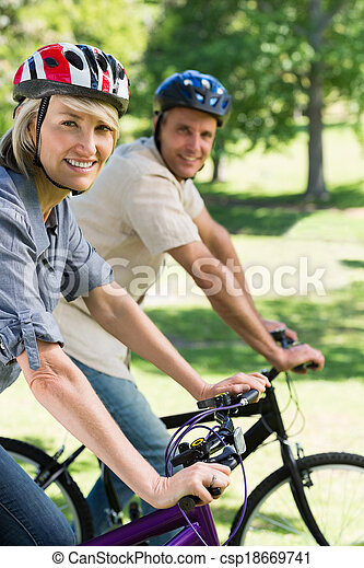 Couple riding bicycles in a park - csp18669741