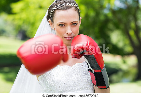 Bride with boxing gloves punching in park - csp18672912