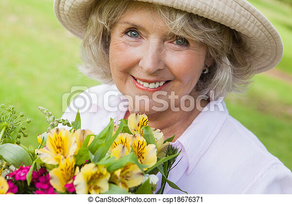 Close-up of smiling mature woman holding flowers at park - csp18676371