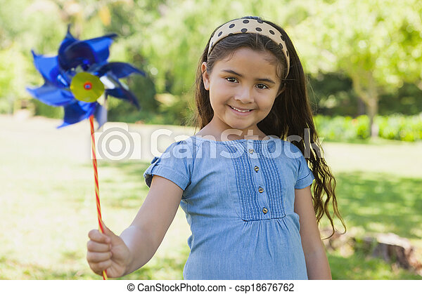 Cute little girl holding pinwheel at park - csp18676762