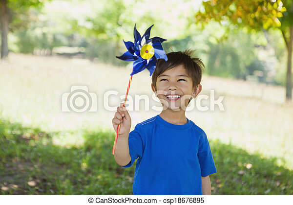 Happy cute little boy holding pinwheel at park - csp18676895