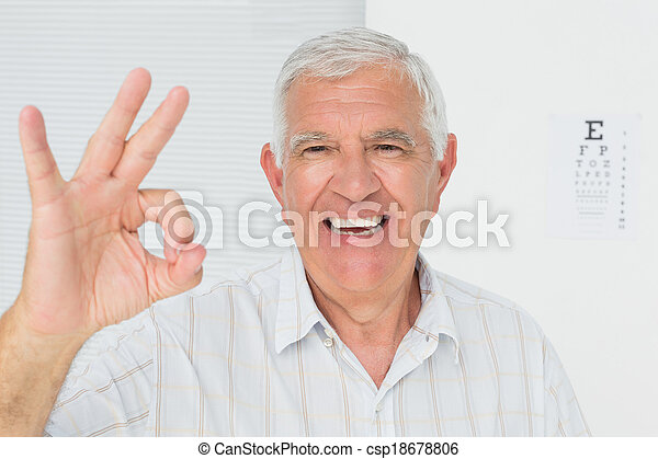 Smiling senior man gesturing ok with eye chart in background - csp18678806