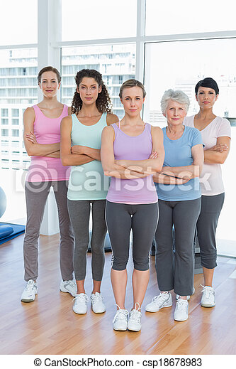 Confident women with arms crossed in yoga class - csp18678983
