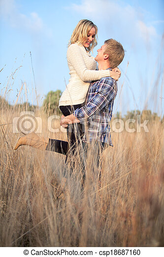 Young adult man holding his girlfriend up - csp18687160