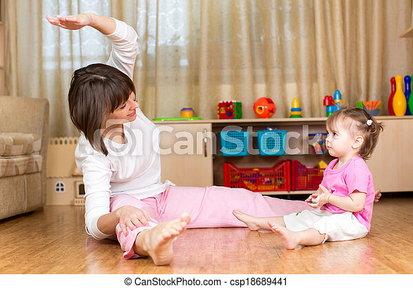 Mom and kid doing exercises sitting on the floor in home interior - csp18689441