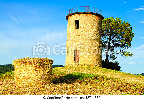 Tuscany, Maremma typical countryside sunset landscape with hill, tree, straw bales and rural tower. - csp18711550